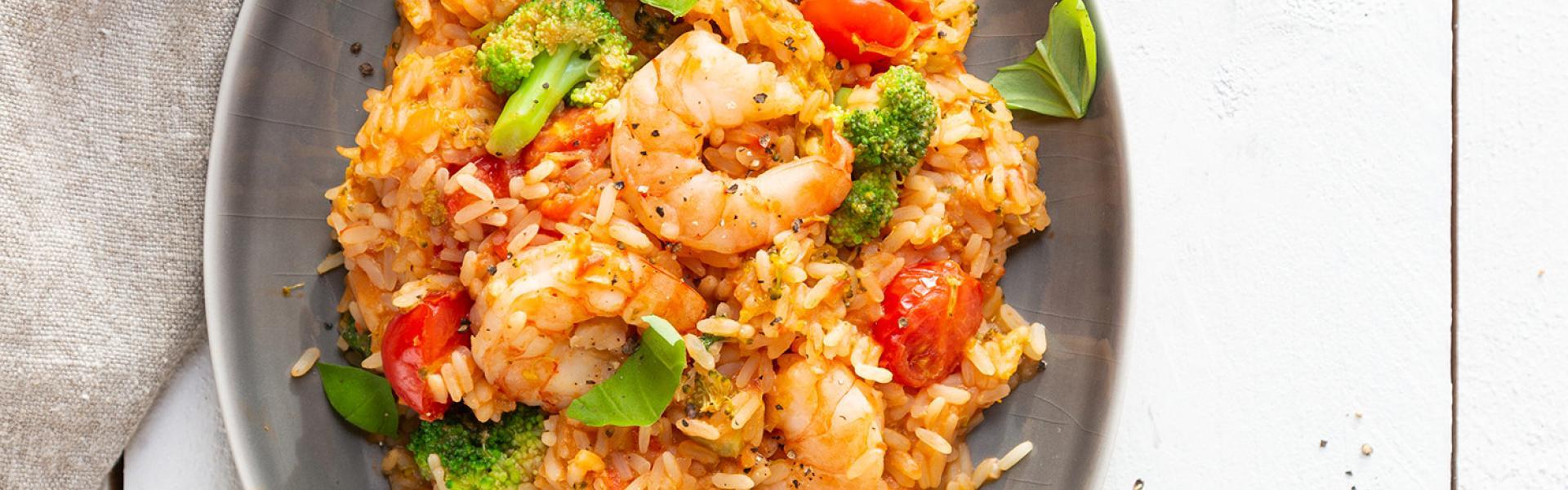 Reispot mit Garnelen und Brokkoli auf einem Teller angerichtet.