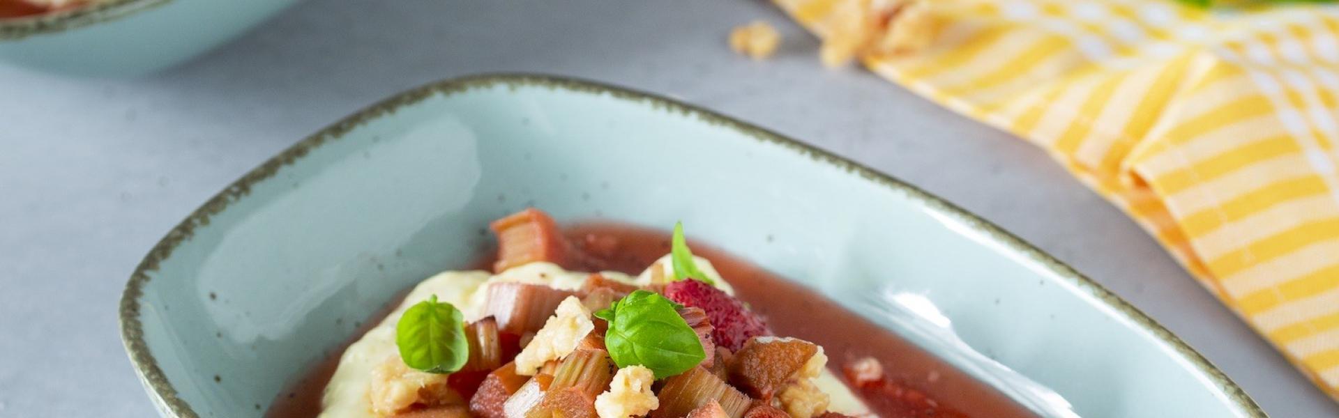 Rhabarber-Erdbeer-Kompott mit Vanillepudding in einem tiefen Teller angerichtet.