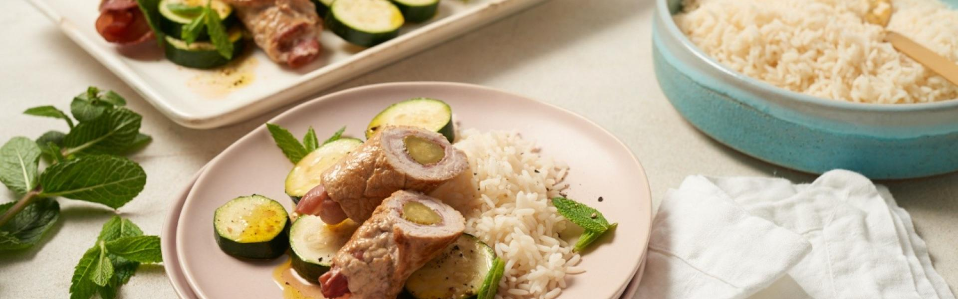 Schnitzelrollen mit Zucchini und Reis auf Teller, Schnitzelrollen auf Servierplatte, Reis in Schüssel