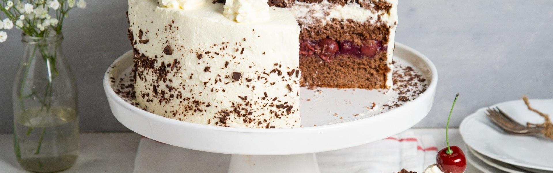 Torte auf Tortenplatte mit Vase und Kuchenstück auf Teller