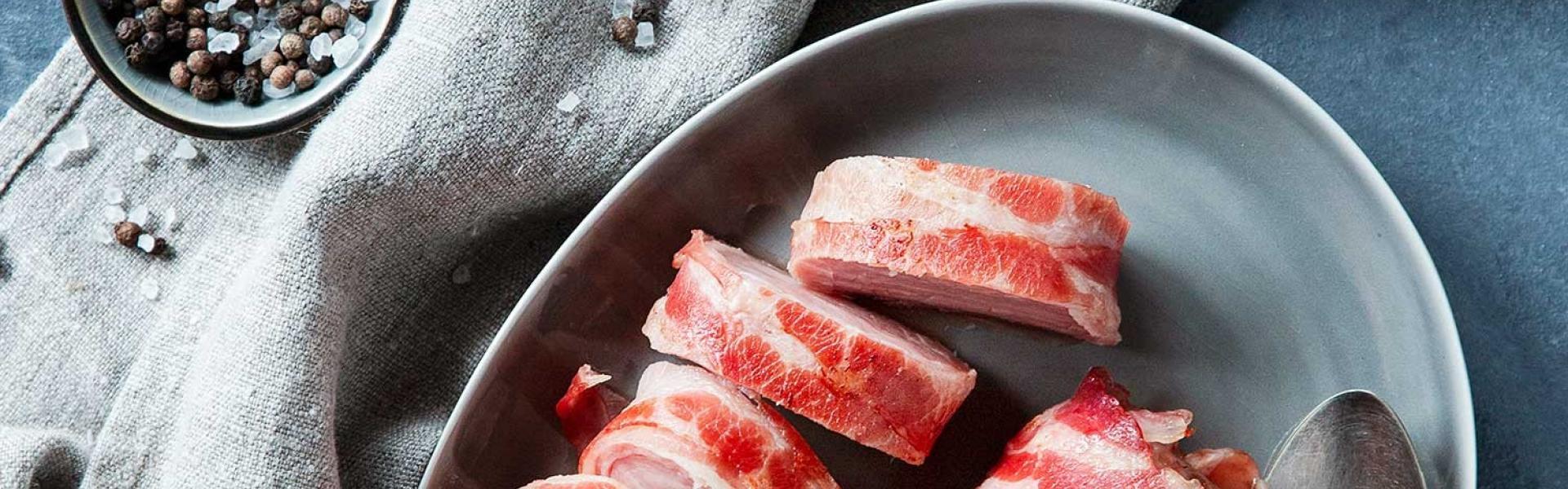 Schweinefilet im Speckmantel angeschnitten auf einem Teller.