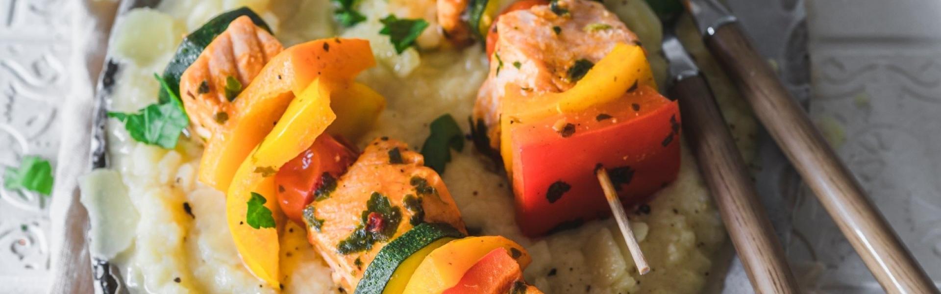 Selleriepüree mit Lachs-Gemüse-Spießen auf einem Teller angerichtet.