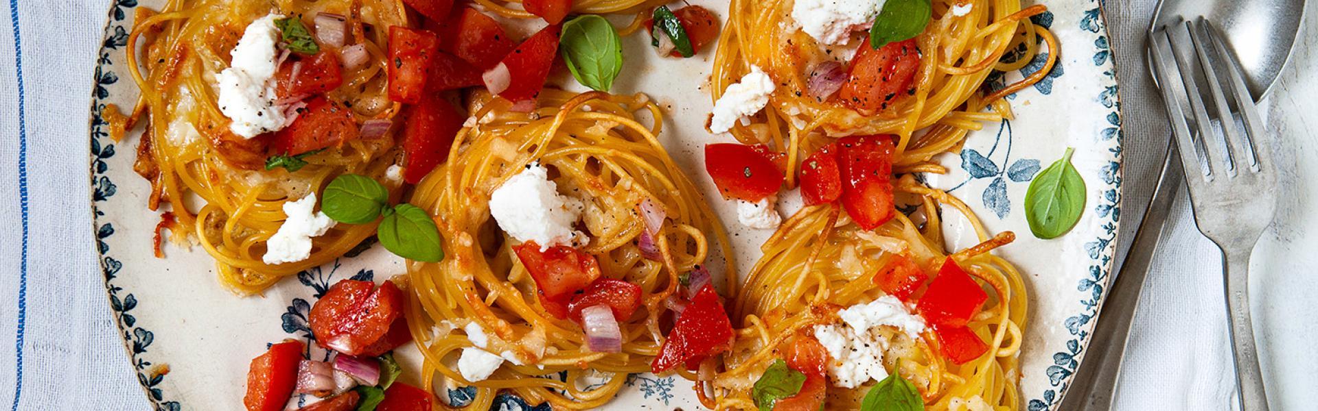 Mehrere Spaghetti Nester auf einem Teller angerichtet.
