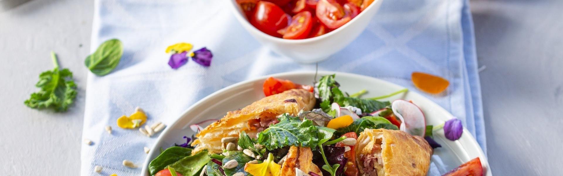 Spargel in Blätterteig auf einem bunten Salat in einem Teller. Daneben Tomaten, Radieschen, Blätterteigtaschen.