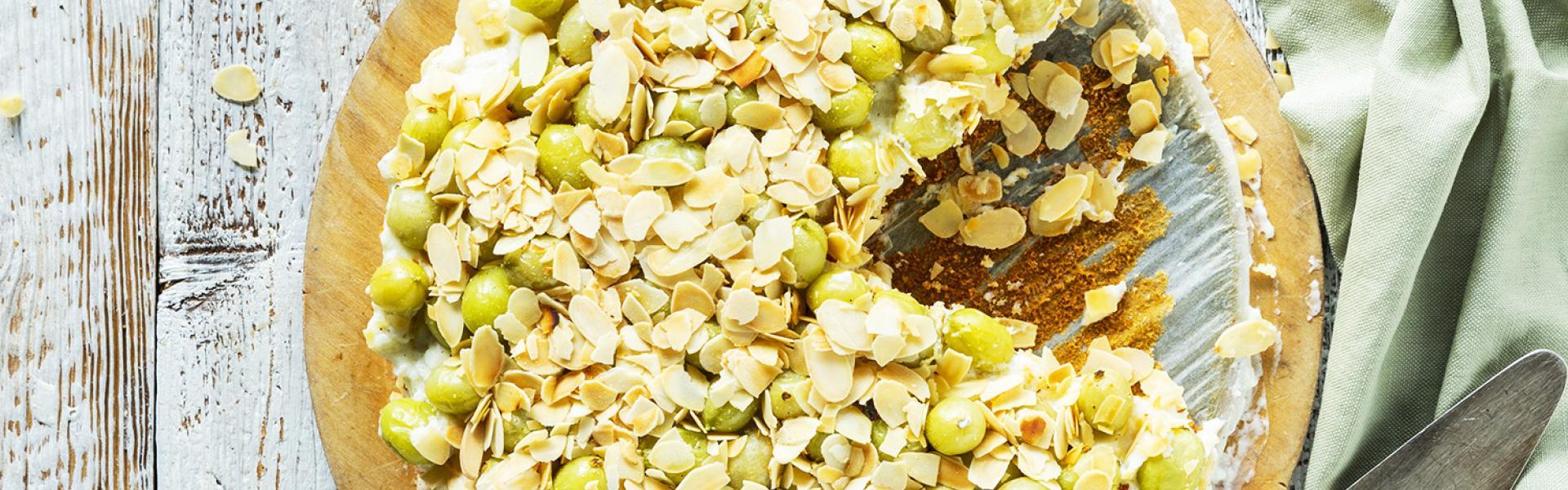 Stachelbeerkuchen mit Pudding und Mandeln angeschnitten auf einer Kuchenplatte mit angelegtem Tortenheber.