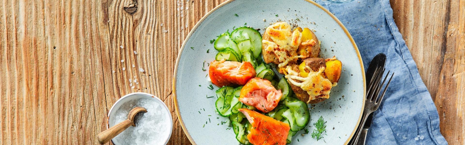 Stampfkartoffeln mit Stremellachs und Gurkensalat auf einem Teller angerichtet.