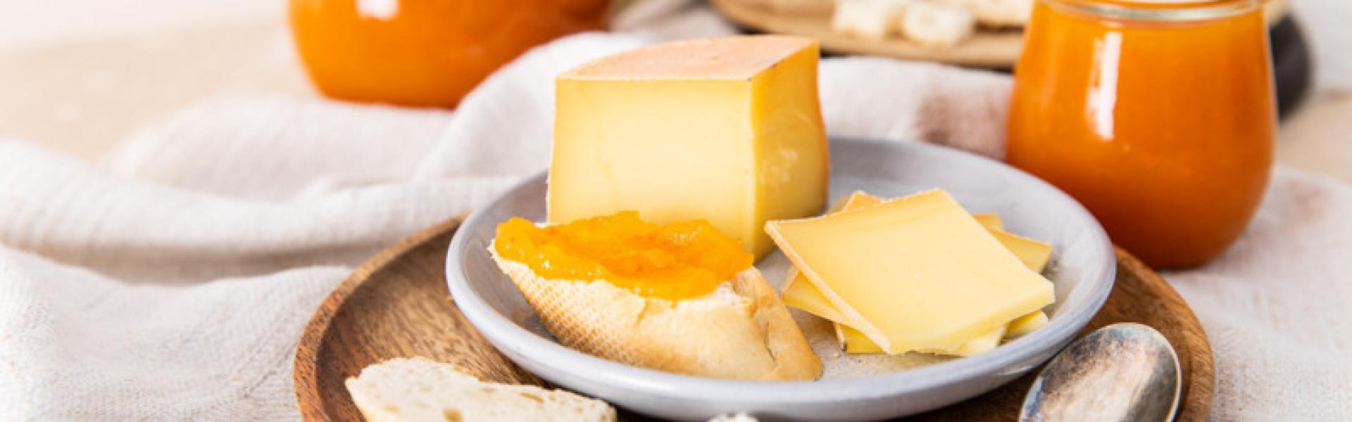Süße Kürbismarmelade auf einem Brot neben Käse auf einer Platte.