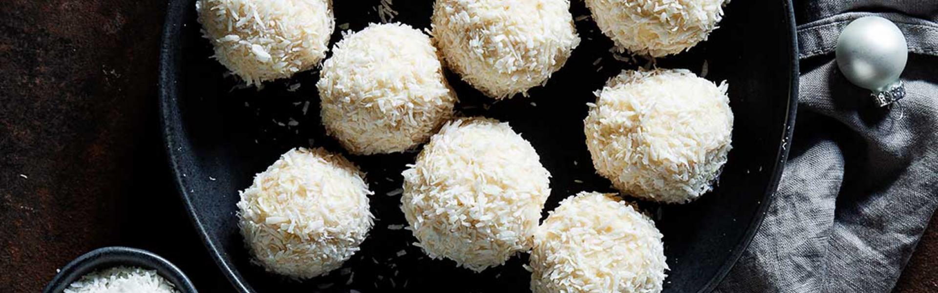 Viele Schneebälle mit Kokos auf einem Teller.