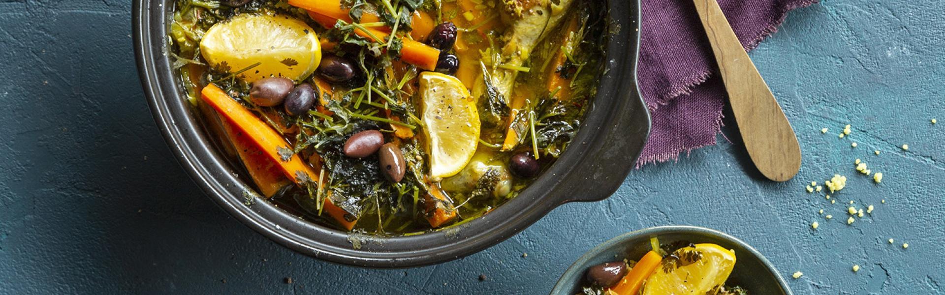 Tajine mit Zitronenhähnchen in der Tajine angerichtet. Drumherum eine Schale mit Couscous und dem Gericht.