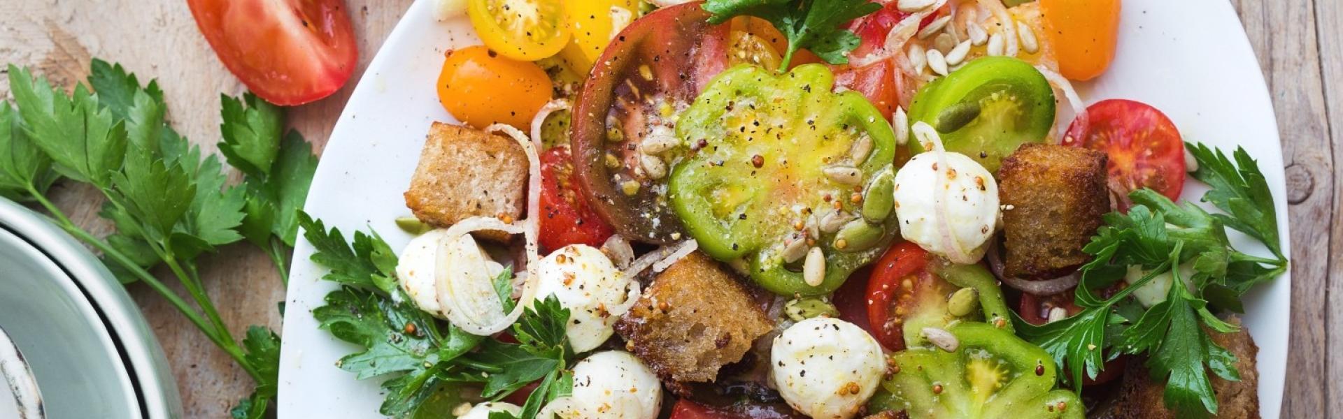 Tomaten-Brot-Salat mit Mozzarella auf großer weißer Platte angerichtet.