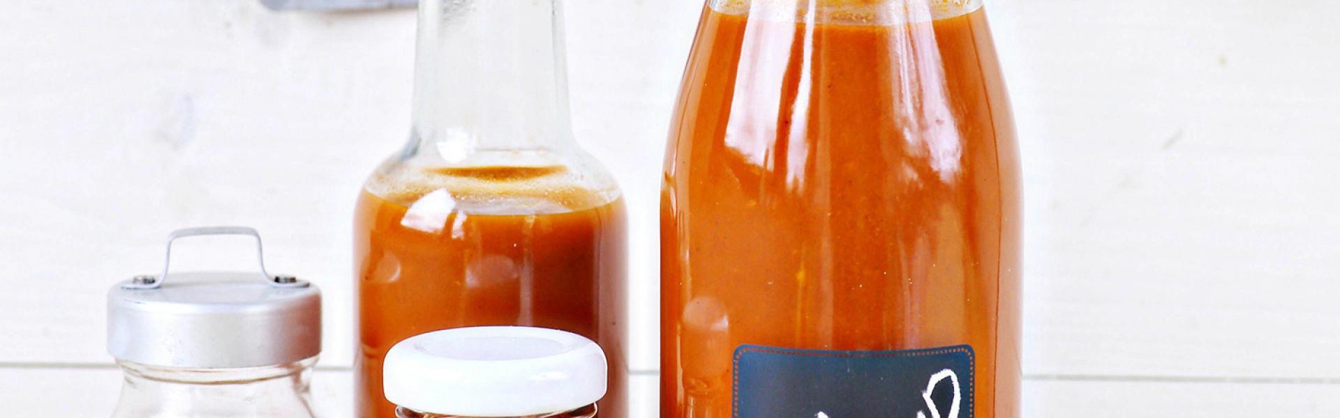 Tomatenketchup in mehreren Flaschen und Schraubgläsern.