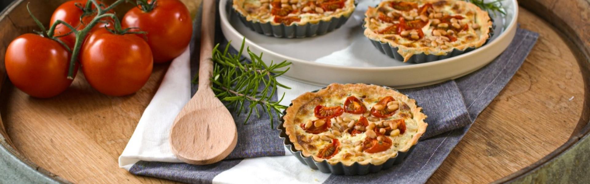 Drei kleine Tomatentartes mit Pinienkernen auf Teller und Holztisch.