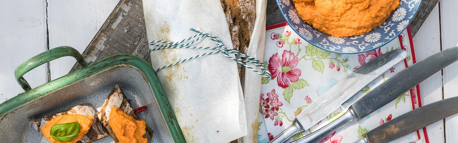 Walnuss-Baguette im Ganzen und in Stücken mit Paprika-Aufstrich bedeckt.