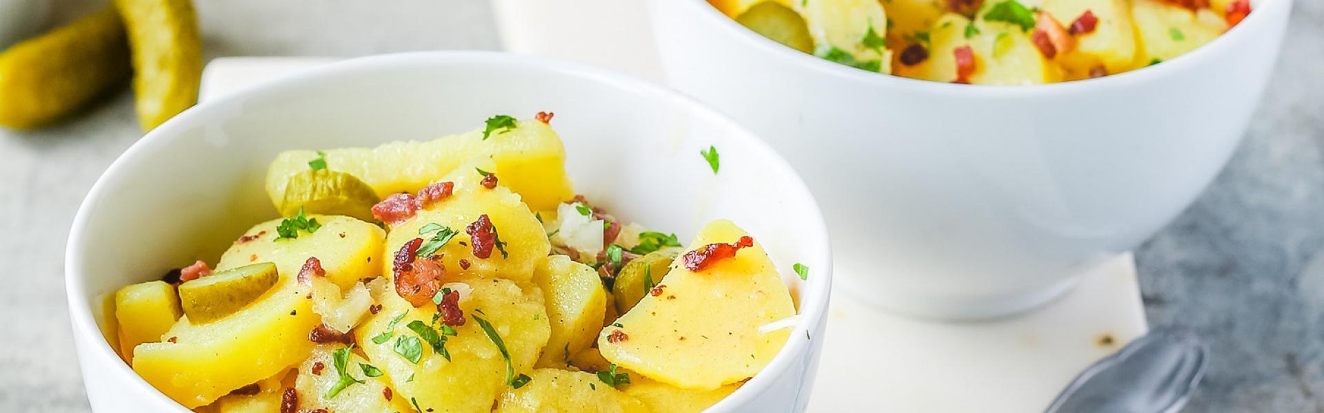 Warmer Kartoffelsalat mit Brühe in zwei Schalen auf einem Brettchen.