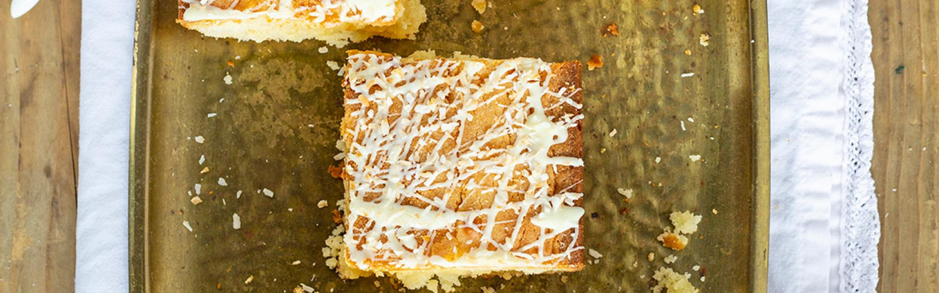 Weiße Schoko-Kokos-Blondies liegen auf einer Servierplatte.