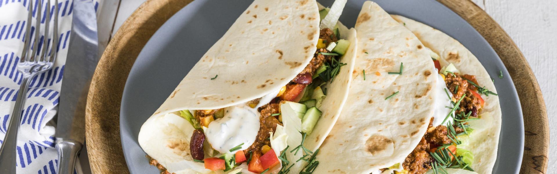 Zwei Wraps mit Chili-sin-Carne-Füllung sind auf einem Teller angerichtet.