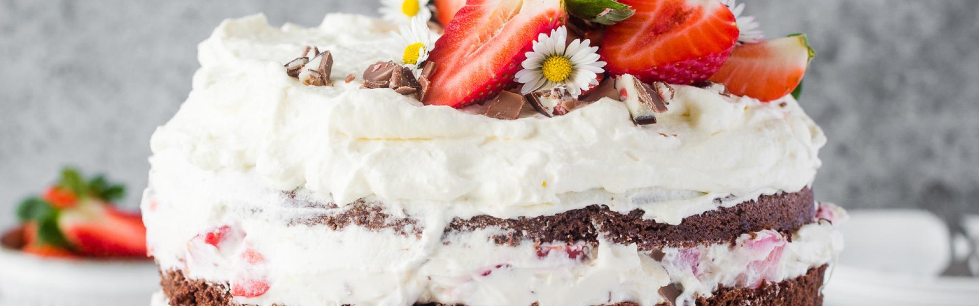 Yogurette-Torte auf weißer Tortenplatte mit Erdbeeren und Sahne dekoriert.