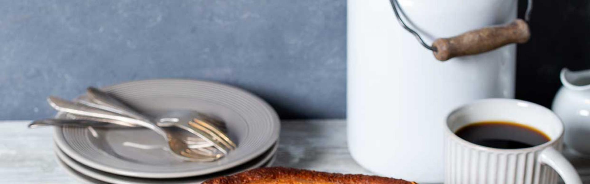 Zimtrolle angeschnitten auf einem gedeckten Kaffeetisch.