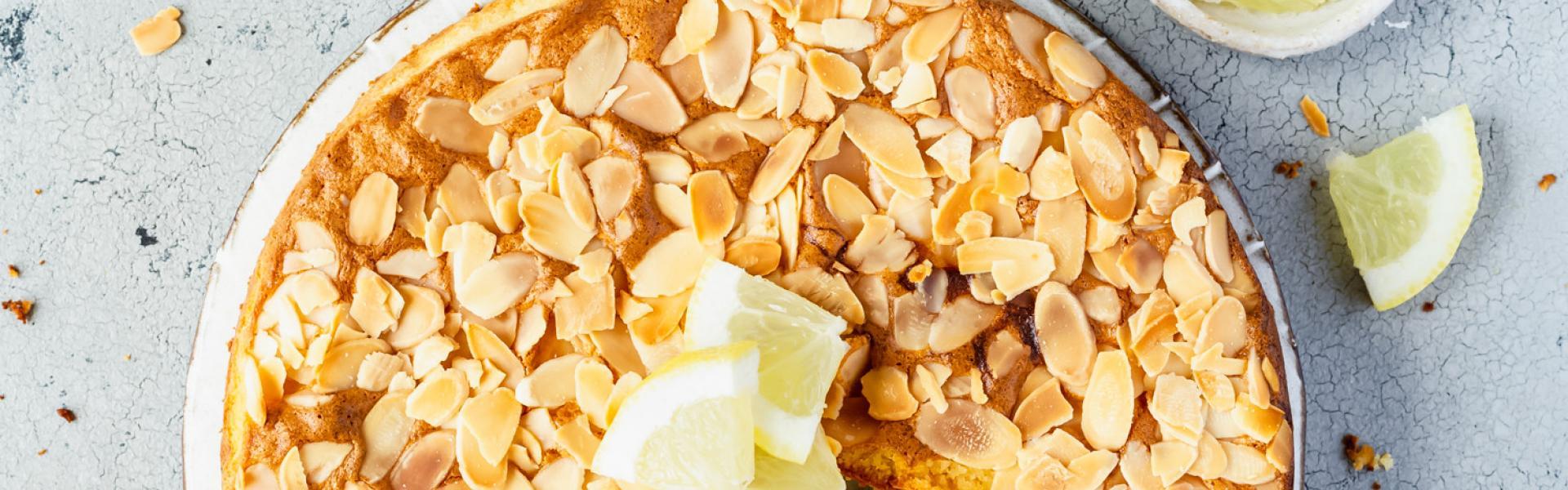 Zitronen-Mandel-Kuchen mit Mandelblättchen und Zitronenscheiben dekoriert und angeschnitten auf einer Kuchenplatte.