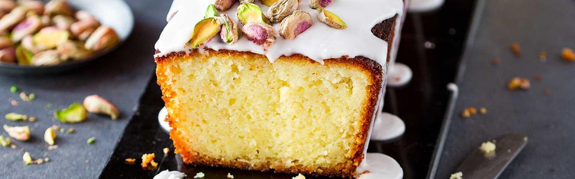 Zitronenkuchen mit Frischkäse und Glasur mit Pistazien auf einem Brett.