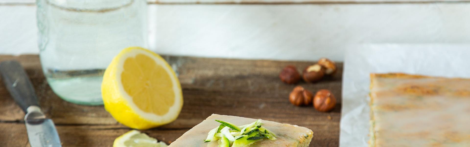 Zucchinikuchen vom Blech in Stücken auf einem Teller angerichtet.
