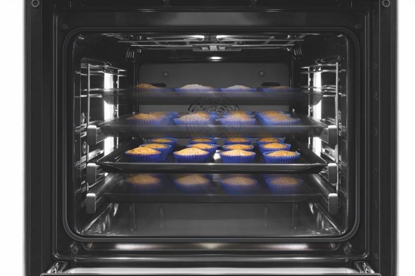 Vier Bleche Muffins in offenem Backofen.