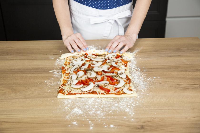 Der belegte Teig für die Pizzaschnecken wird aufgerollt.