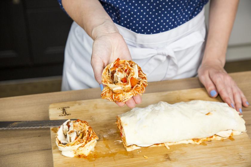 Der gefüllte Teig für Pizzaschnecken liegt auf einem Brett. Zwei Stücke sind abgeschnitten.