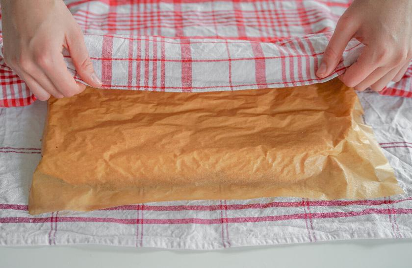 Die gestürzte Biskuitrolle wird mit einem Küchentuch bedeckt