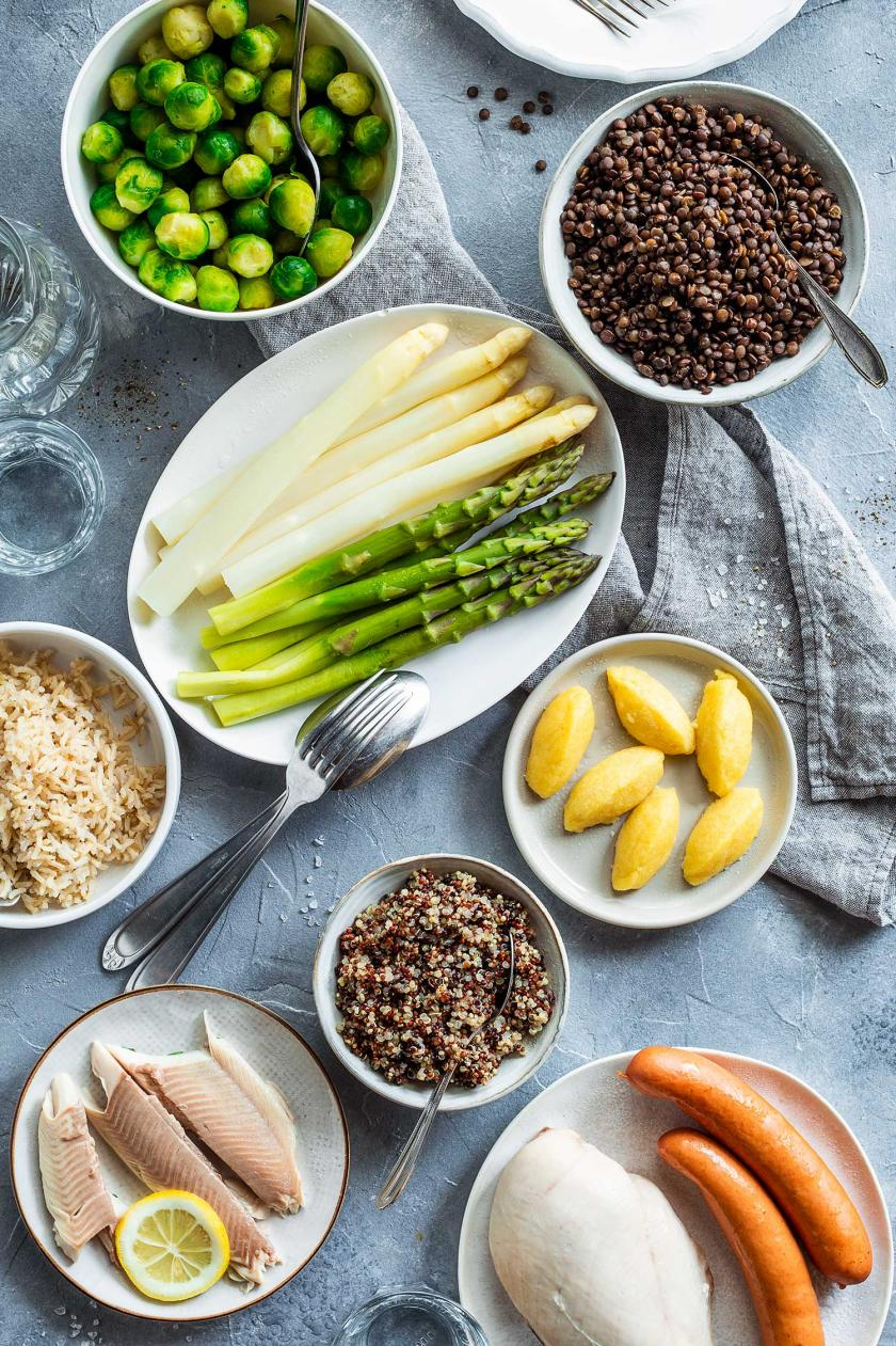 Gedämpfte Lebensmittel wie Spargel, Fisch, Kartoffeln, Linsen, Rosenkohl und Würstchen auf einem Tisch.