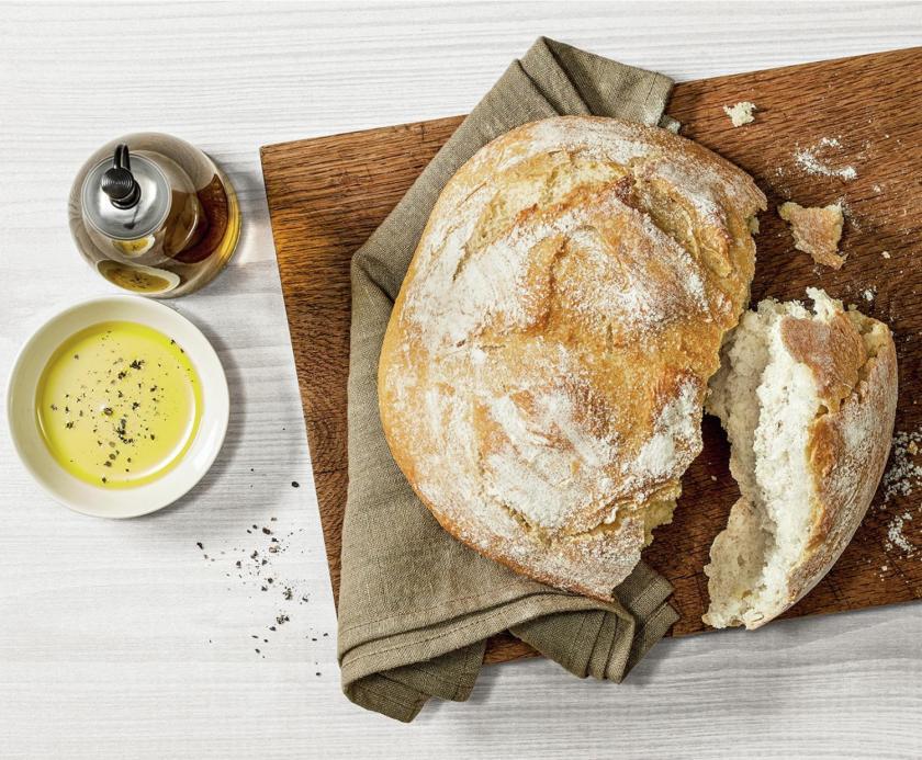 Selsbt gebackenes Brot aufgeschnitten auf Holzbrett mit Olivenöl.