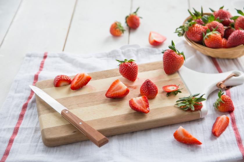 Aufgeschnittene Erdbeeren auf einem Holzbrett