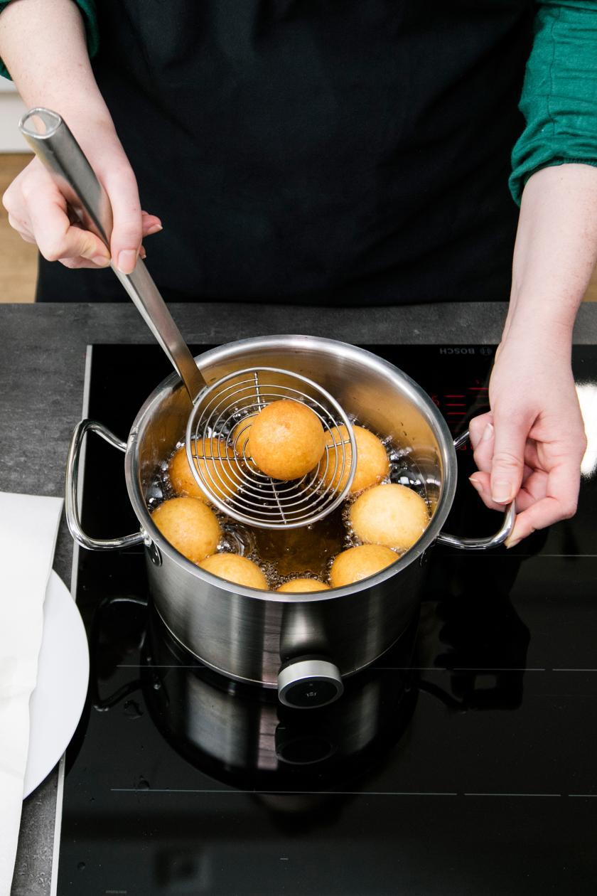 Quarkbällchen werden in einem Topf frittiert.