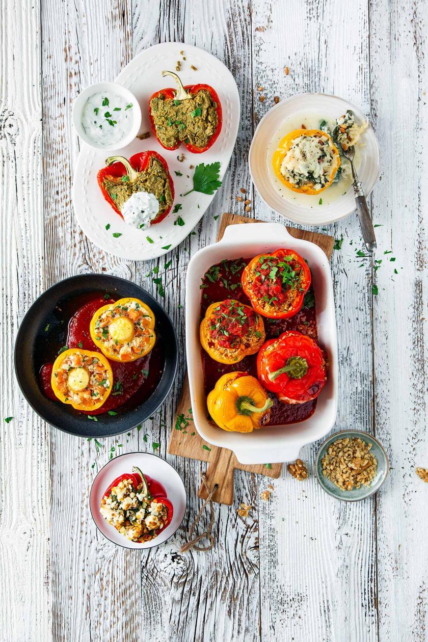 Mehrere vegetarisch gefüllte Paprika auf einem Tisch zusammengestellt.