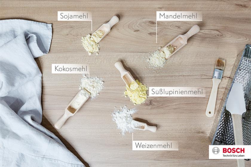 Kleine Schaufeln mit verschiedenen Mehlsorten für glutenfreie Kuchen auf einem Holzbrett verteilt.