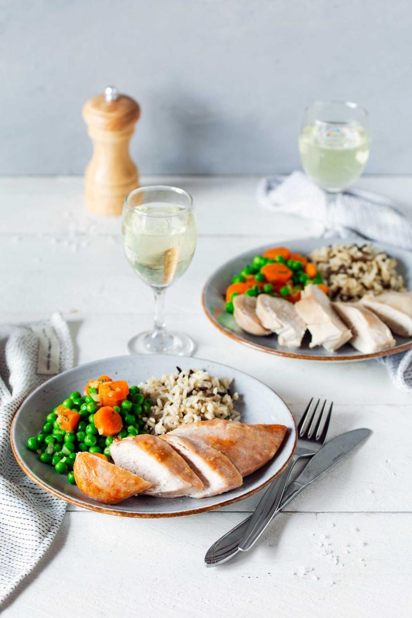 Hähnchenbrust im Ofen gegart auf einem Teller mit Erbsen und Reis.