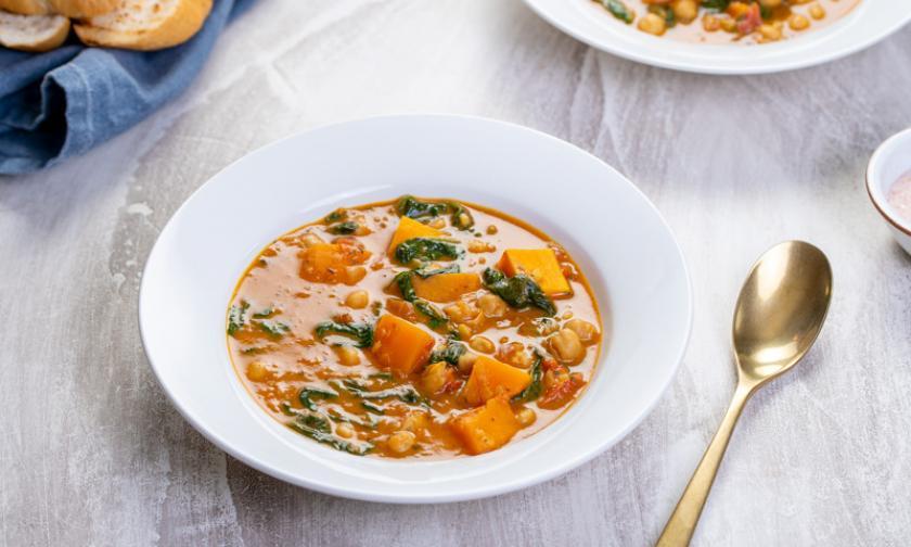Süßkartoffel- und Kichererbsen-Curry mit Spinat auf Tellern.