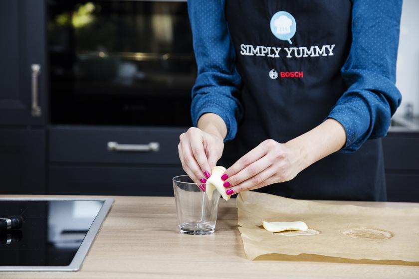 Glückskekse mit Spruch werden mit Hilfe von einem Glasrand geformt.