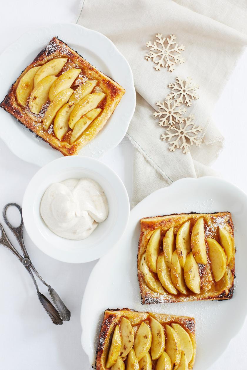 Apfel-Blätterteig-Taschen auf Tellern auf einem Tisch.