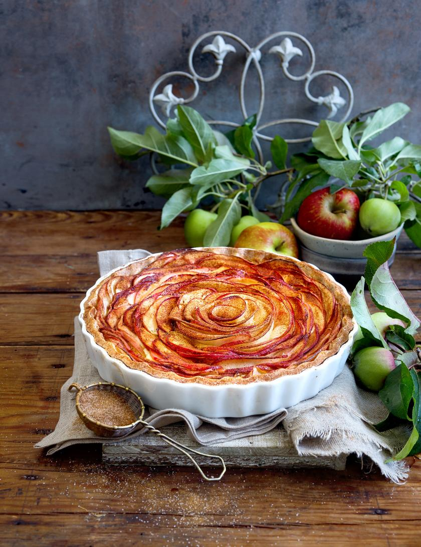 Apfelkuchen Dinkelmehl in einer Form auf einem Tisch.