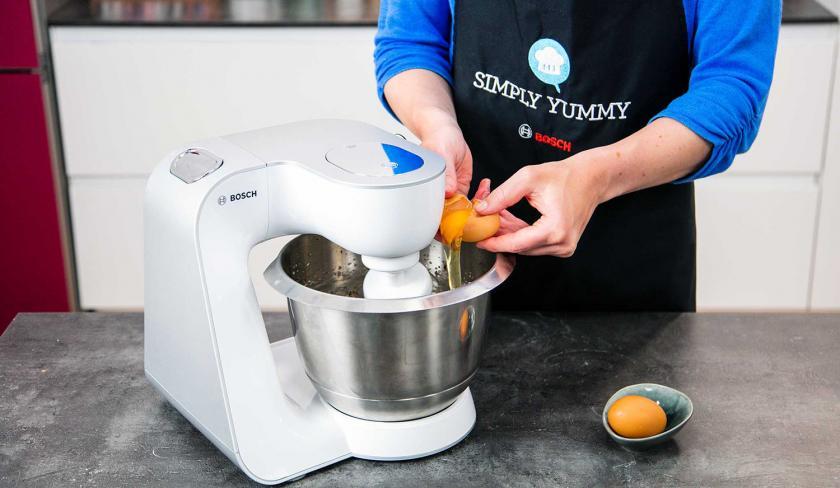 Für den Teig der Apfelmusmuffins wird ein Ei in die Rührschssel einer Küchenmaschine gegeben.