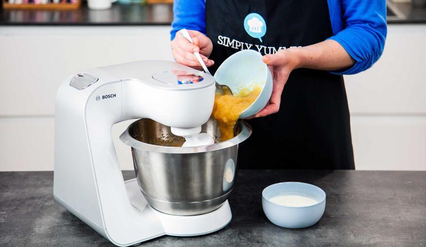 Apfelmus wird in die Rührschüssel einer Küchenmaschine gegeben.