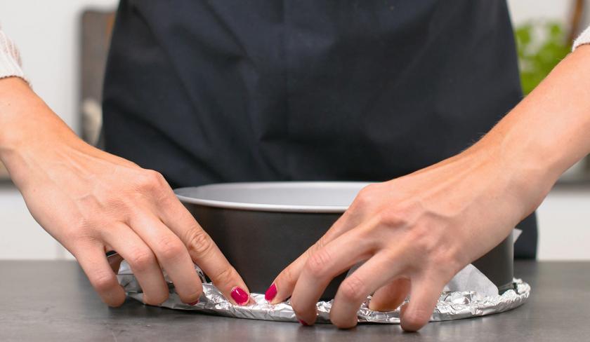Die Backform für den Aprikosen-Upside-Down-Cake wird in Alufolie eingeschlagen.