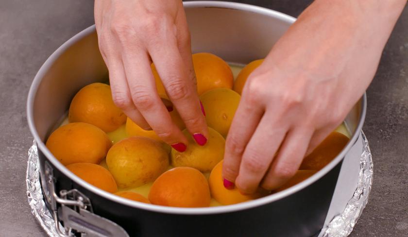 Für den Aprikosen-Upside-Down-Cake werden Aprikosen in der Form verteilt.