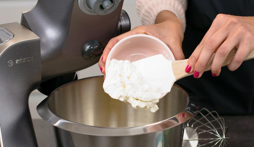 Für den Teig des Aprikosen-Upside-Down-Cake wird Ricotta in die Schüssel einer Küchenmaschine gegeben.