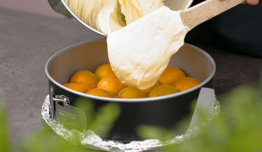 Für den Aprikosen-Upside-Down-Cake wird der Teig auf den Früchten verteilt.