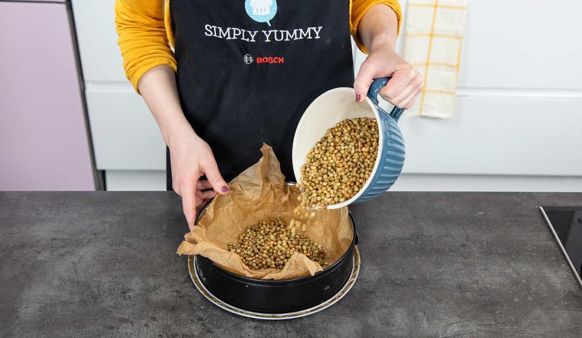 Backerbse werden in eine Springform mit Backpapier gegeben zum Vorbacken des Aprikosenkuchen mit Streuseln.