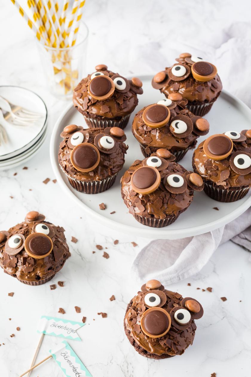 Acht Bärenmuffins auf Tortenplatte mit goldenen Strohhalmen und Partydeko.