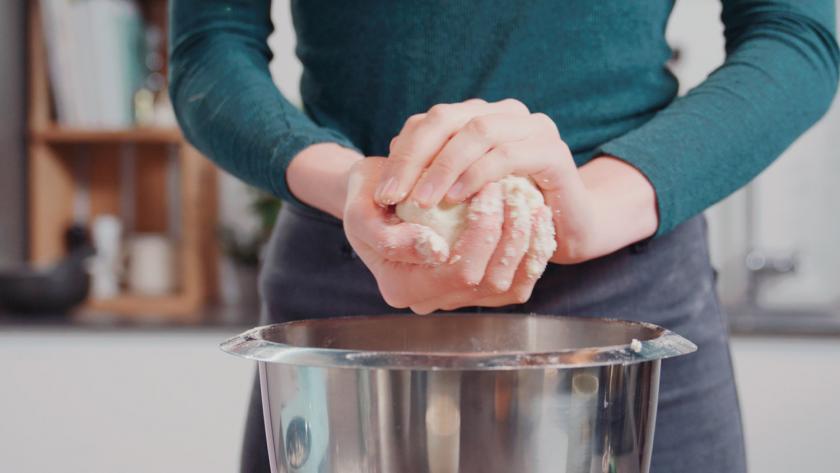 Teig wird in der Hand zur Kugel geformt.