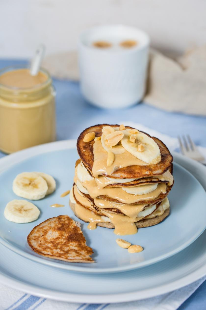 Bananen-Pancakes mit Erdnussbutter gestapelt auf einem Teller